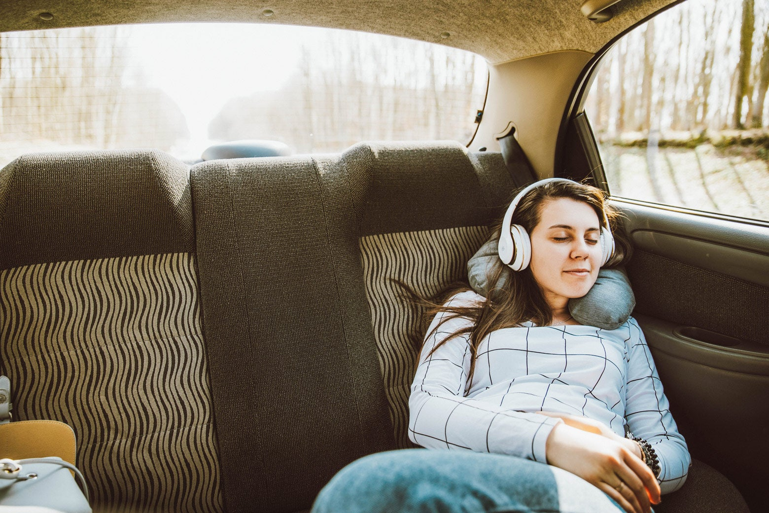 Woman listens to Slate podcasts through headphones in a car