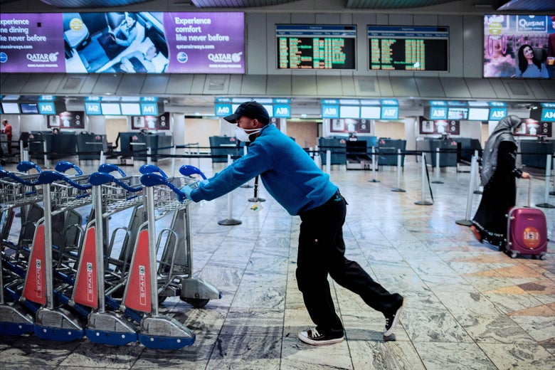 An Airports Company South Africa (ACSA) employee wears a face mask while pushing trolleys at the international departures terminal at the O.R. Tambo international airport in Johannesburg, on March 17, 2020.