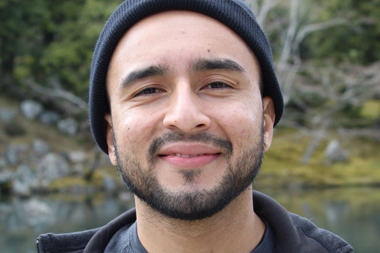 A smiling young man with a beard looks directly into the camera.
