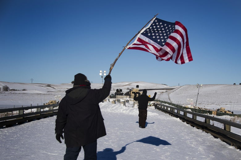 A man waves a U.S. flag as another man with arms raised walks toward a barricade.