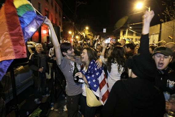 Revelers display U.S. and gay pride flags as they celebrate early election returns favoring Washington state Referendum 74.