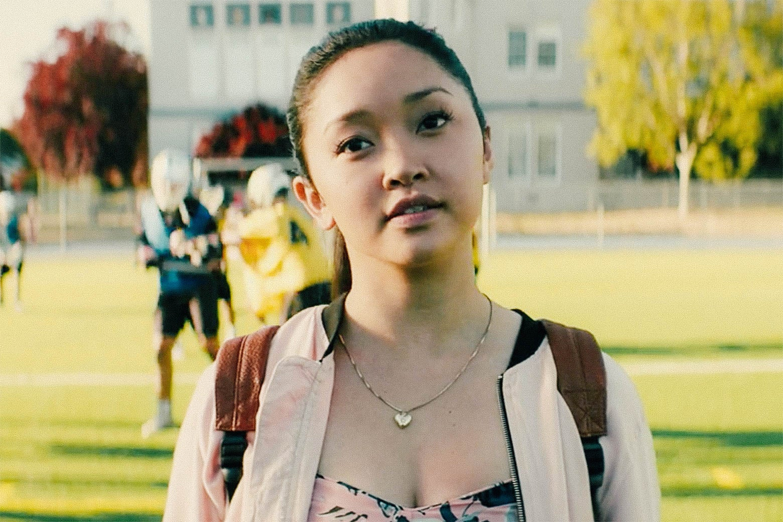 In a scene from To All the Boys I've Loved Before, Lara Jean (Lana Condor) stands on a lacrosse field, looking forward wistfully.