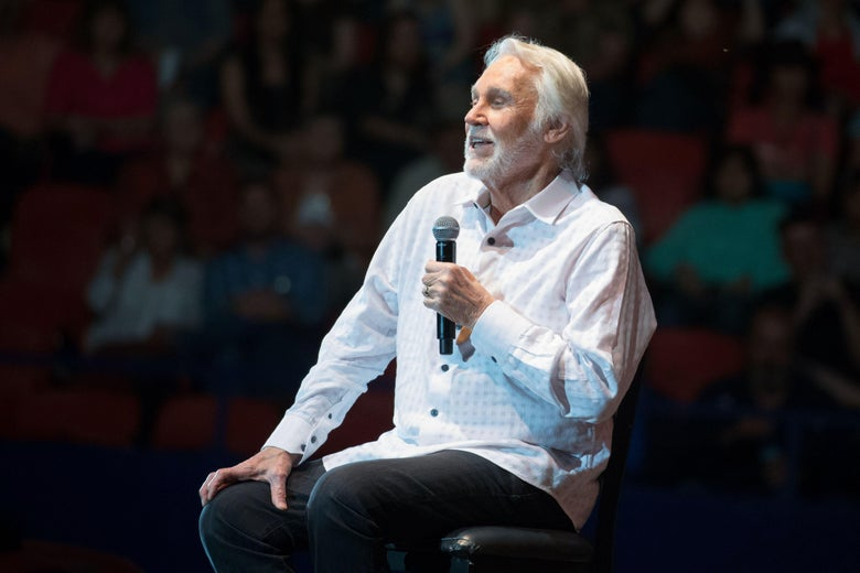 Kenny Rogers sits on stage holding a microphone.