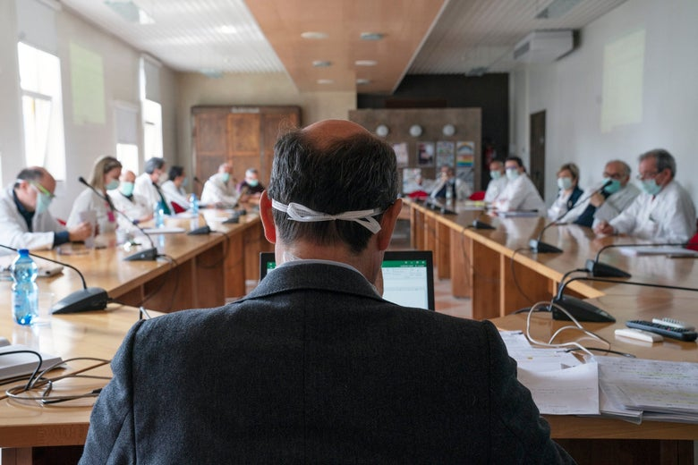 A man in a suit wearing a surgical mask briefs a conference room full of masked doctors.