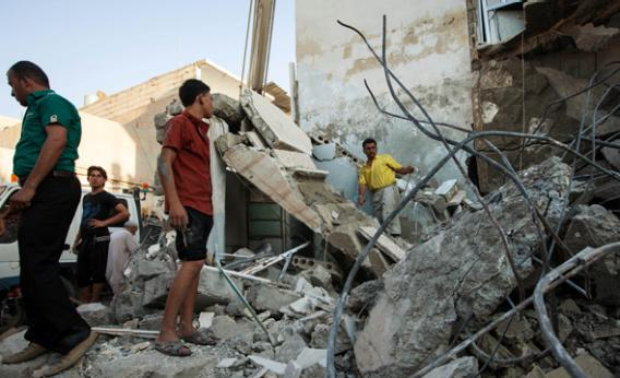 Syrians inspect debris after a bomb hit a building during clashes between rebel fighters and Syrian government.