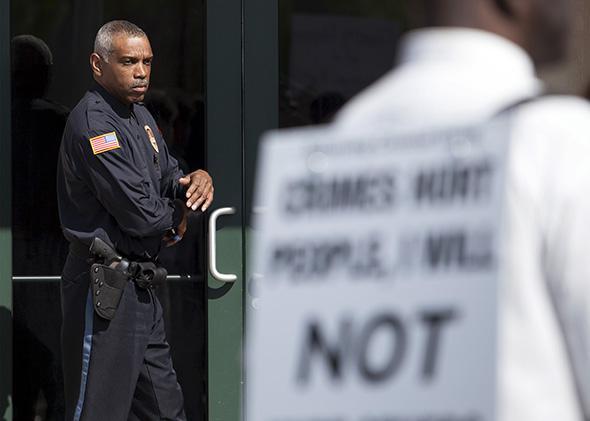 police officer watches protestors at a rally in North Charleston, South Carolina.