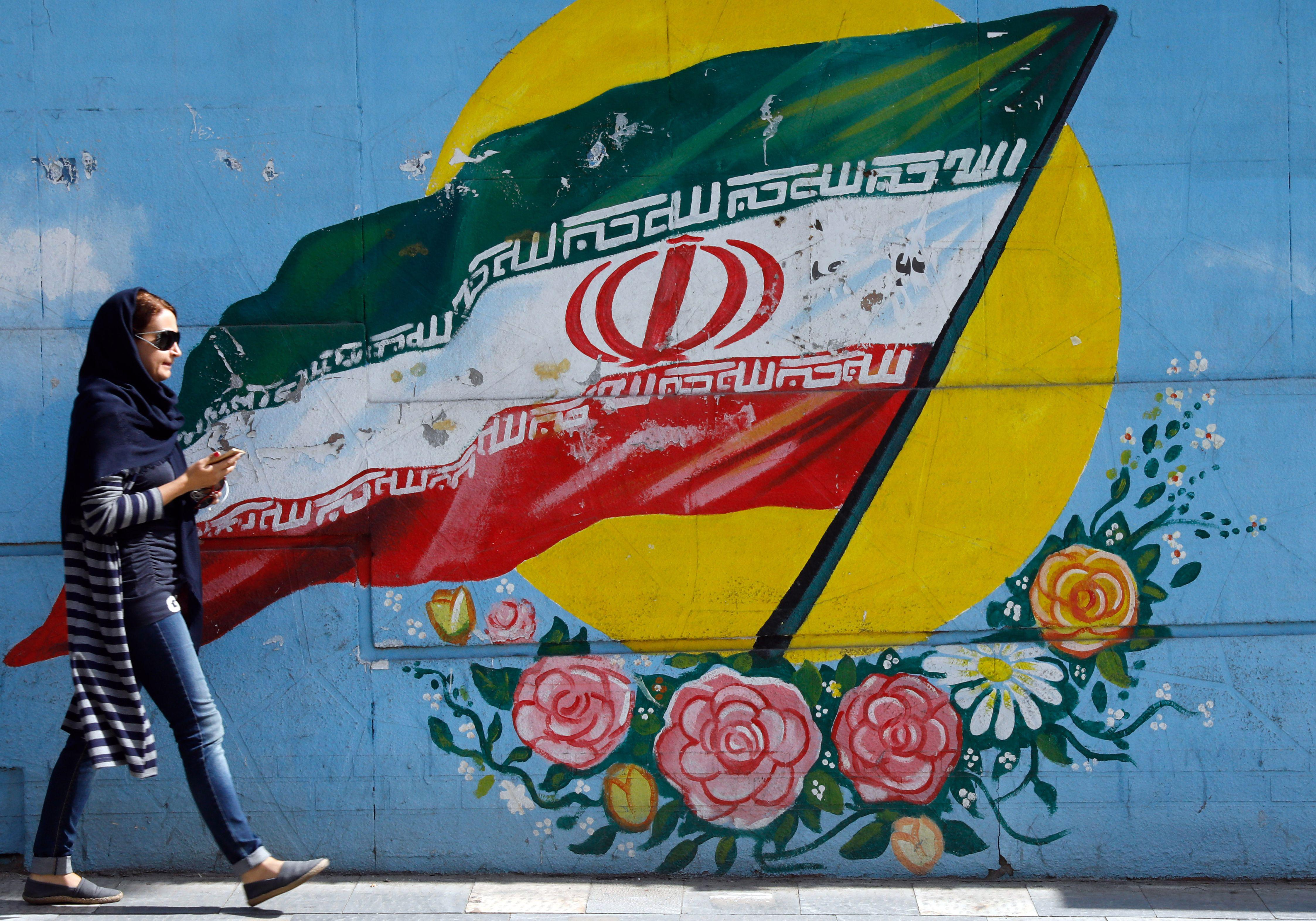 An Iranian woman walks past a mural of the Iranian flag in the capital Tehran, on October 14, 2017.         Iranians responded with anger and mockery on Saturday to the bellicose criticism of their government by US President Donald Trump who threatened to tear up the landmark nuclear deal. / AFP PHOTO / STR        (Photo credit should read STR/AFP/Getty Images)