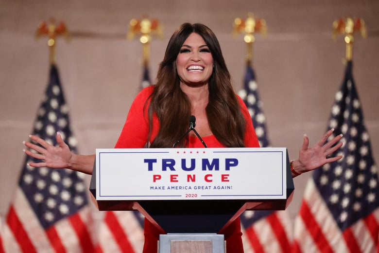Kimberly Guilfoyle smiles and holds her arms out wide from behind a podium that says Trump Pence.