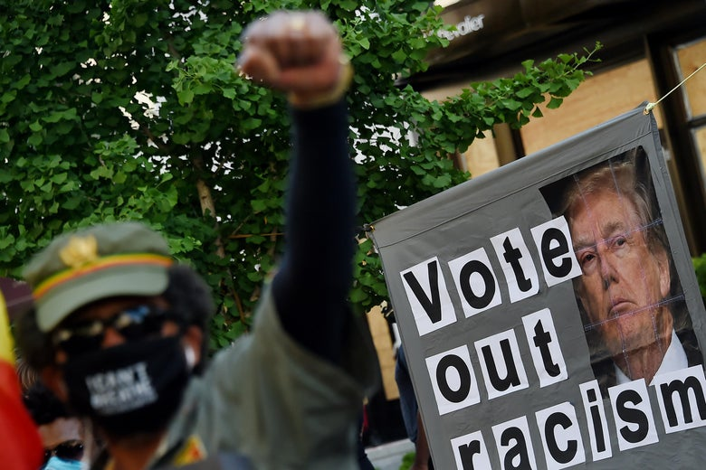 """A demonstrator raises a fist in front of a sign that says """"Vote Out Racism"""" with a picture of President Donald Trump."""