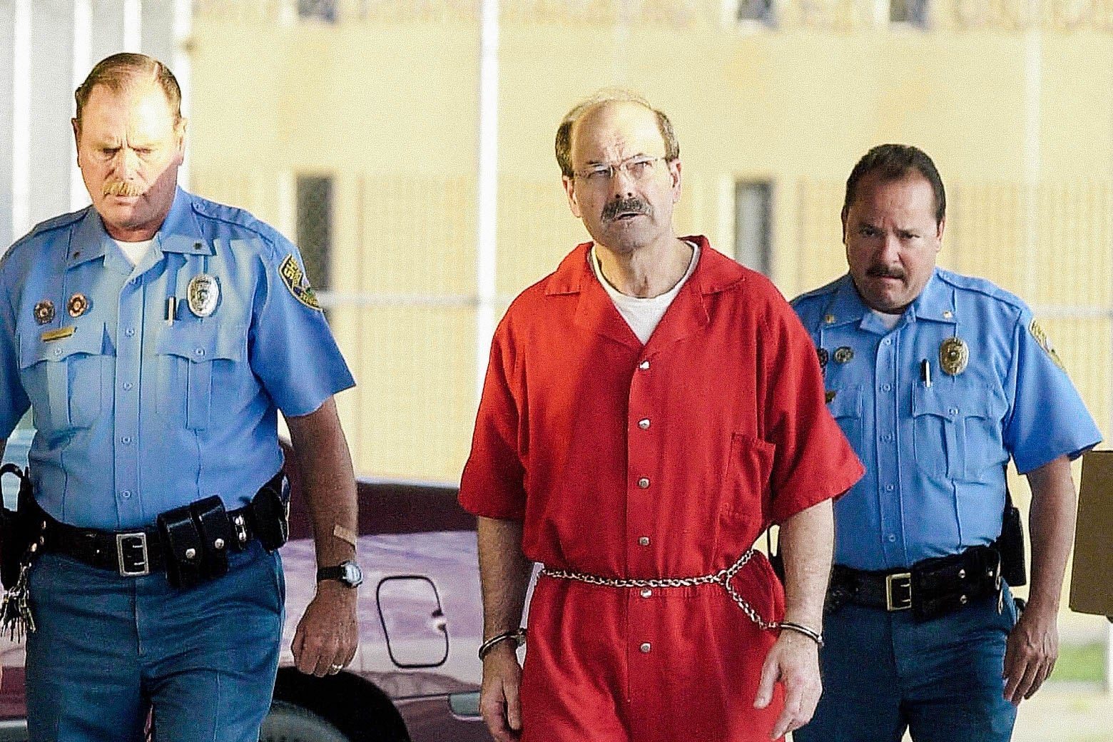 Dennis Lynn Rader wearing prison jumpsuit and handcuffs.