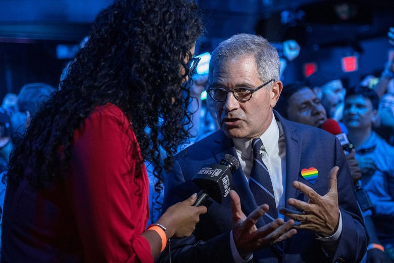 Krasner talks to a reporter amid a crowd of people.
