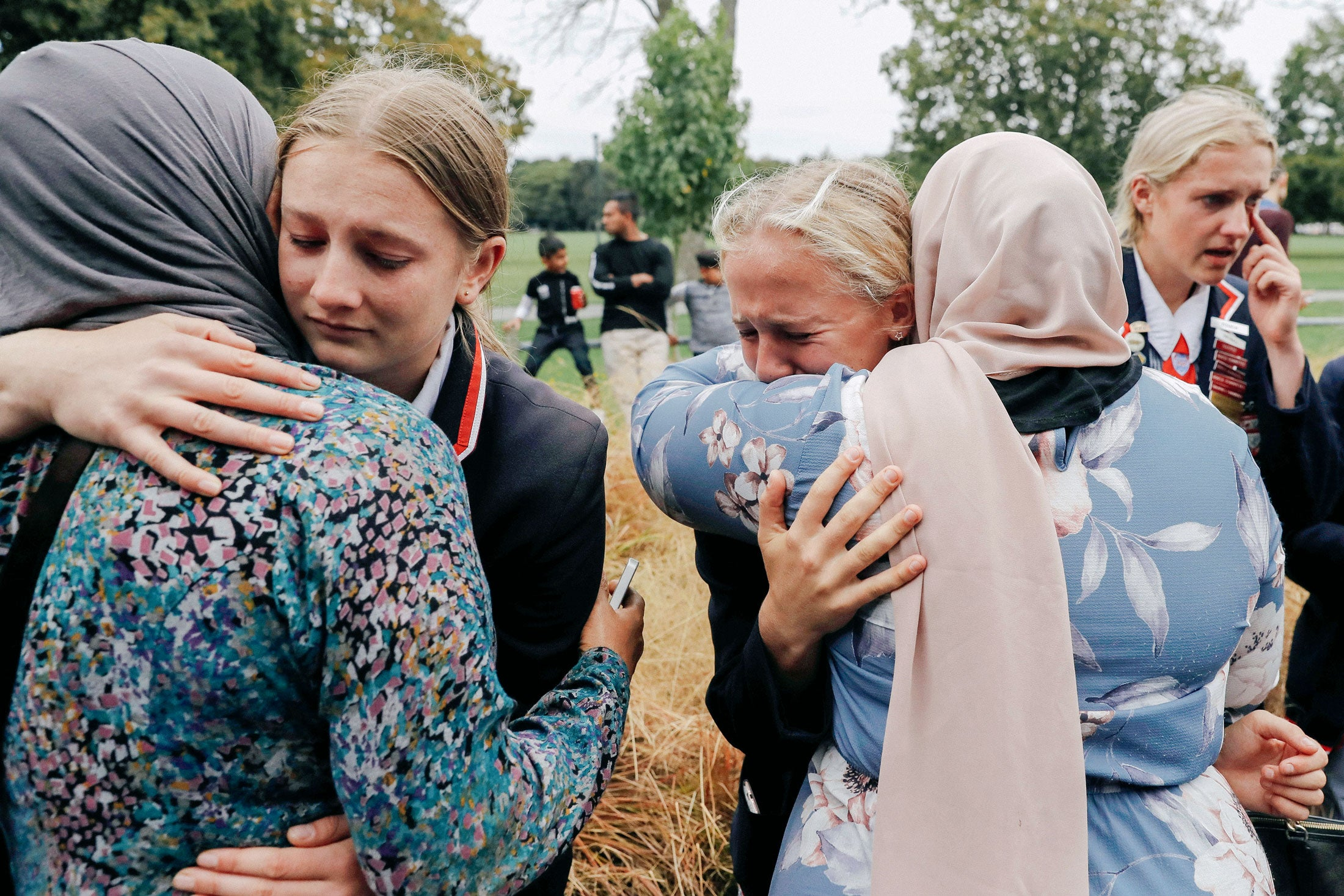 High school students from a Christian school embrace Muslims waiting for news of their relatives following Friday's shooting in Christchurch, New Zealand.