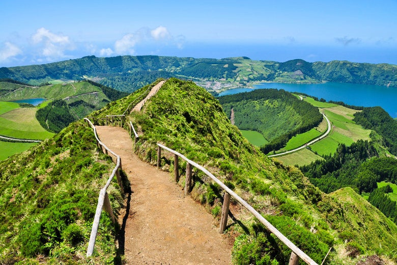 Landscape shot of a path through the hills of the Azores with lush greenery and clear blue skies.