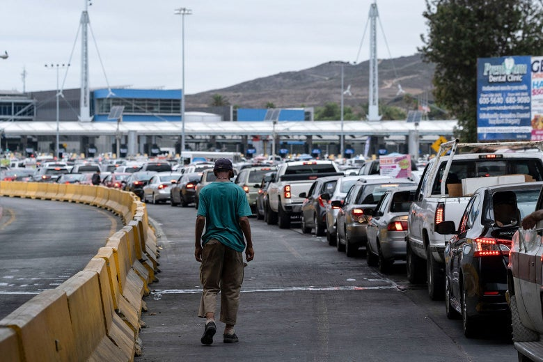A man walks alone beside a line of cars stopped at the border crossing.