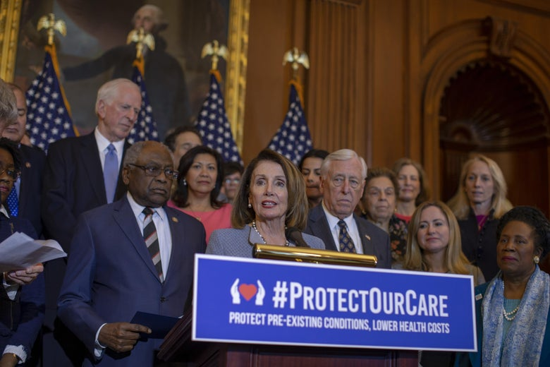 "Pelosi, flanked by Steny Hoyer and other Democrats, speaks at a podium that has a ""Protect Our Care"" sign on it."