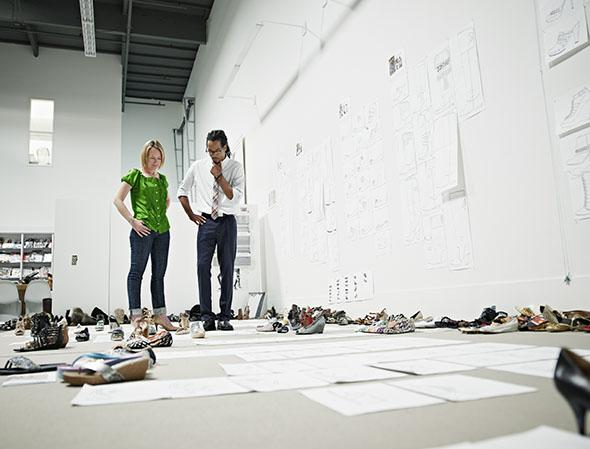Designers examining sample shoes on floor.