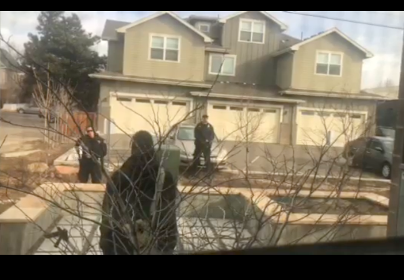 In a blurry screengrab from the video, the man can be seen from behind. Two officers across the street face the camera. One of them has his hand at his hip.
