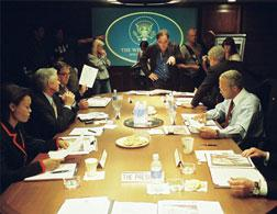 Director Oliver Stone (standing, center) on the set of his film W., with (left to right, seated) Condoleezza Rice (Thandie Newton), Donald Rumsfeld (Scott Glenn), George Tenet (Bruce McGill), George W. Bush (Josh Brolin, seated on table), Colin Powell (Jeffrey Wright) and Dick Cheney (Richard Dreyfuss). Photo credit: Sidney Ray Baldwin. Click image to expand.