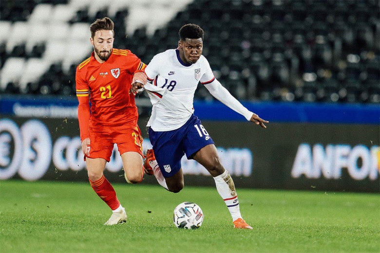 Yunus Musah dribbles a soccer ball in a game against Wales.