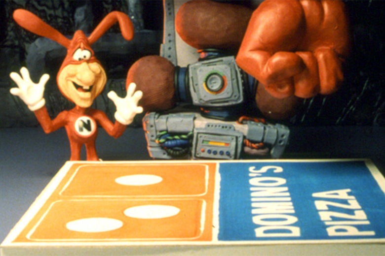 The Domino's noid in a 1980s ad. The noid is a tiny humanoid creature dressed in a red Spandex suit. It has a mask and red bunny ears that are also part of the suit. It has a human face with a big nose and wears white gloves. It stands over a Dominos Pizza box. A gloved human hand hovers off-screen at the top.