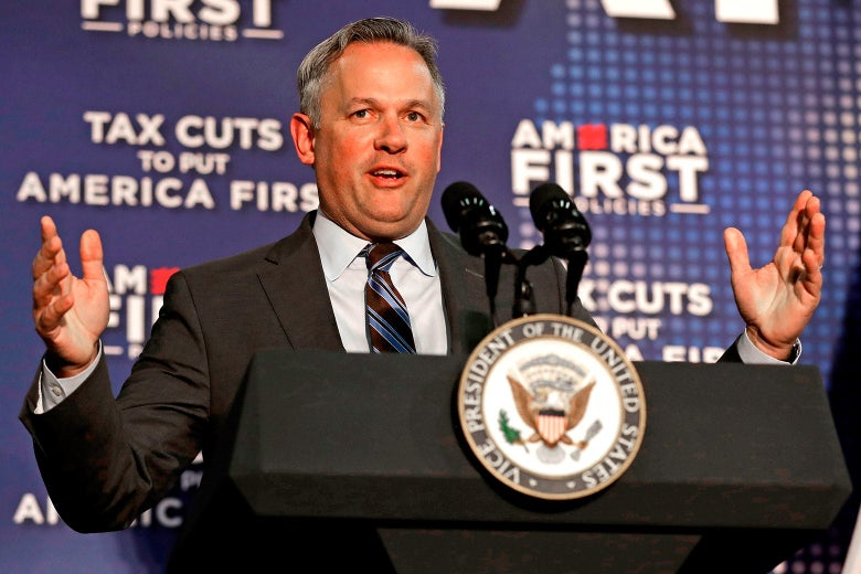 Forest raises his arms while speaking at a podium, with America First signage behind him.