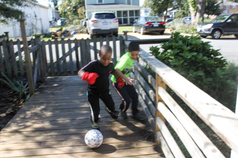 Two boys play with a soccer ball in a fenced-in area.