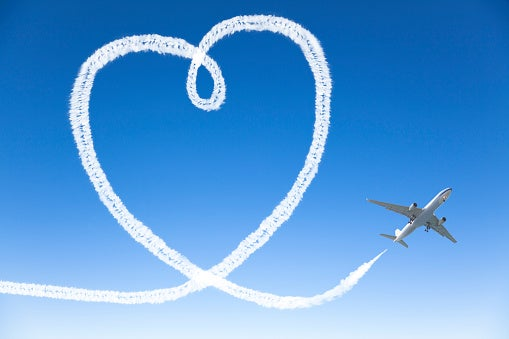 An airplane flying on blue skies, sky-writing a big heart.
