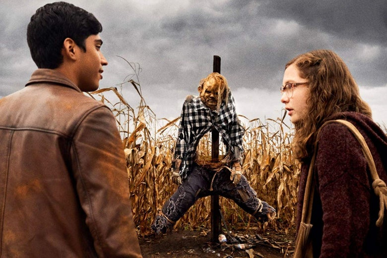 In a scene from the film, two kids stand in front of a menacing scarecrow in a cornfield.