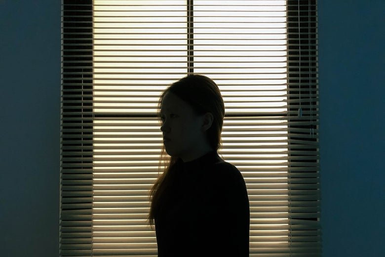 The silhouette of a woman standing in front of a window with the blinds closed.