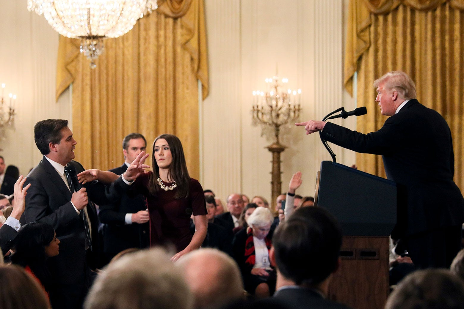 A White House staff member reaches for the microphone held by CNN's Jim Acosta as he questions U.S. President Donald Trump on Wednesday.