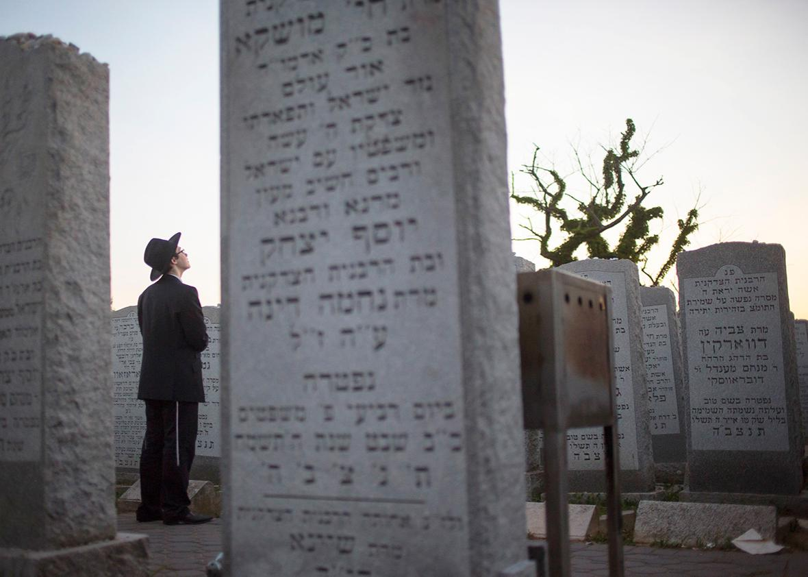 A visitor prays at the gravesite of the Lubavitcher Rebbe, Rabbi Menachem Mendel Schneerson June 30, 2014 at the Old Montefiore Cemetery in the Queens borough of New York.