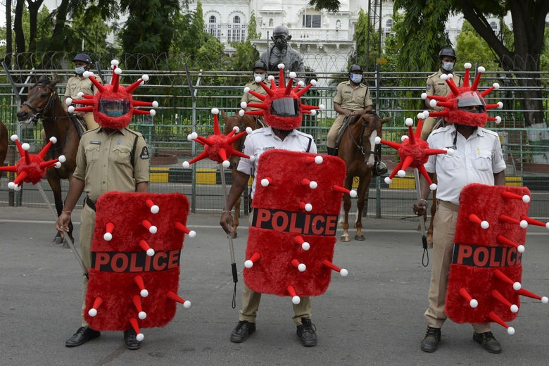 A row of three police officers wearing helmets and holding shields and batons all made to look like the COVID-19 virus (they are covered with red fake fur, cones, and white balls). Behind them, four more police officers stand on horseback.