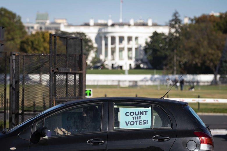 """A van with a sign """"Count the Votes"""" posted on the window is parked outside of the White House gate."""