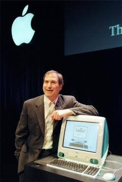 Steve Jobs posing with Apple Computer's iMac.