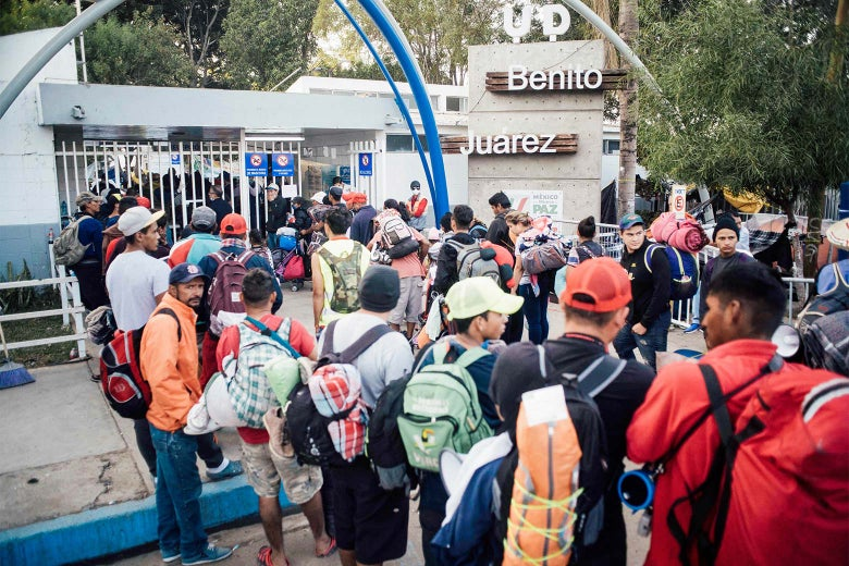 A crowd of people wearing backpacks standing outside of a stadium gate.