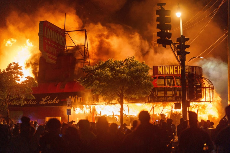 Protesters gather in the street in front of a burning liquor store. Smoke fills the night sky.