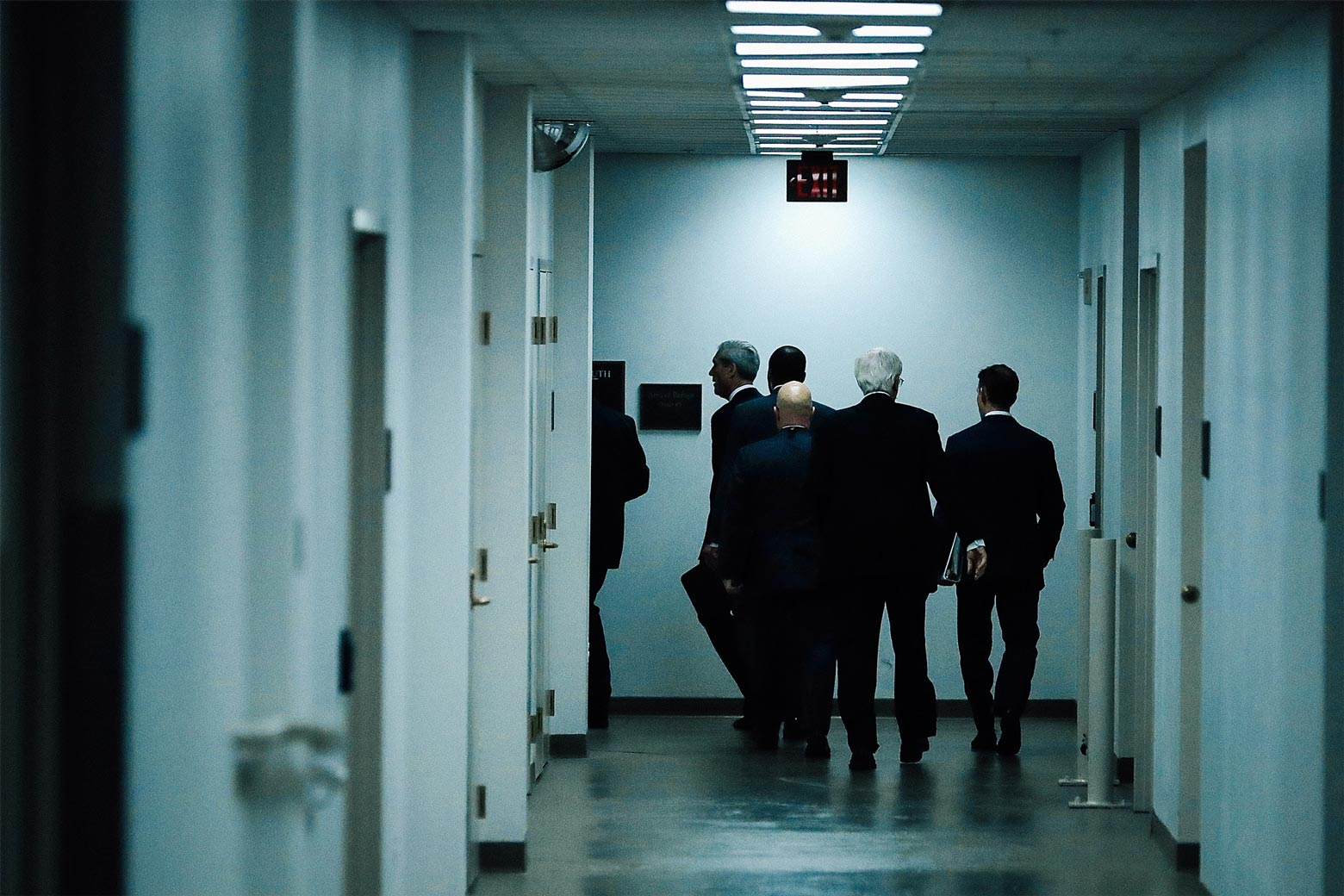 Robert Mueller disappearing into a back hallway.