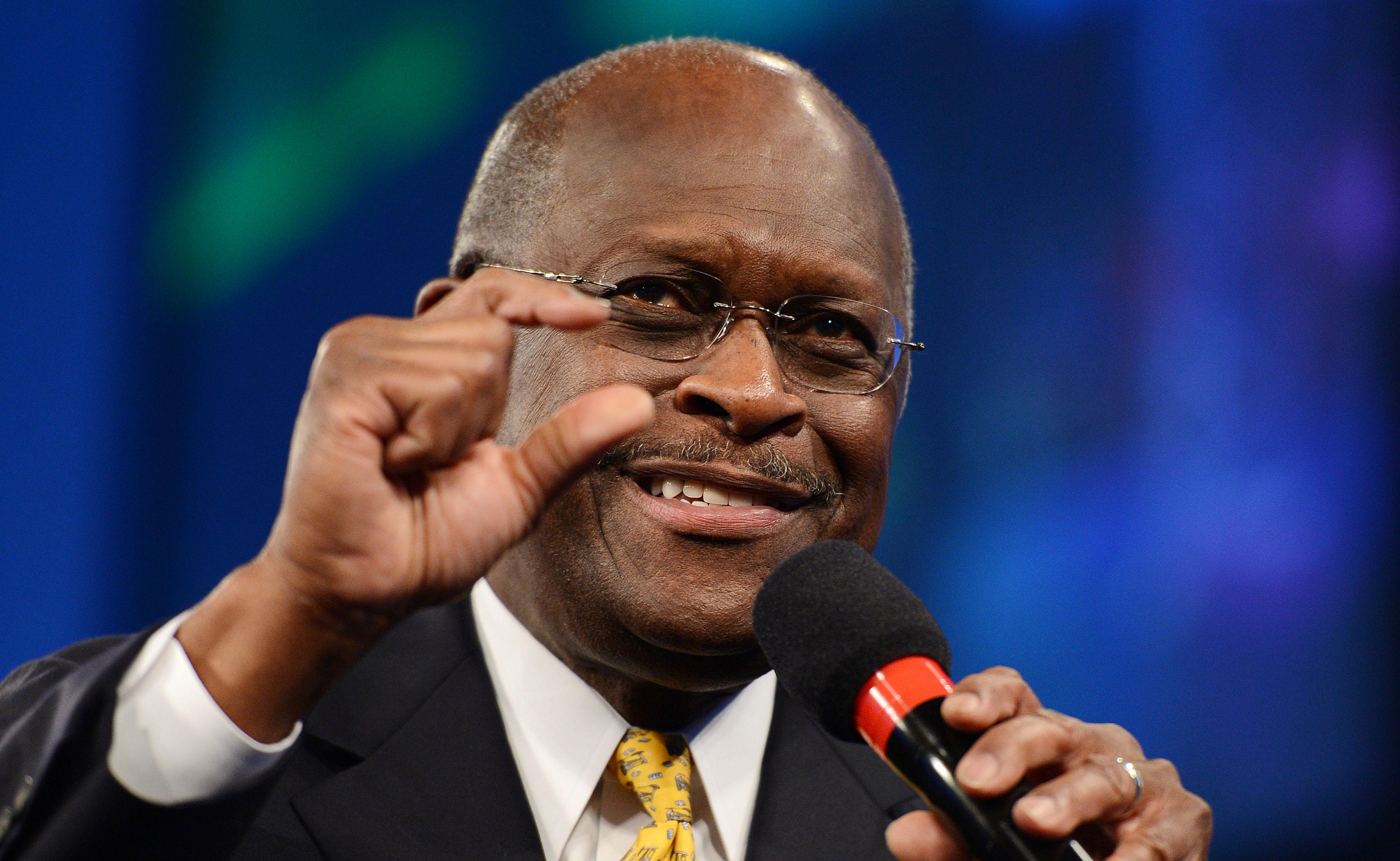 Herman Cain holds a microphone and gestures with his other hand.