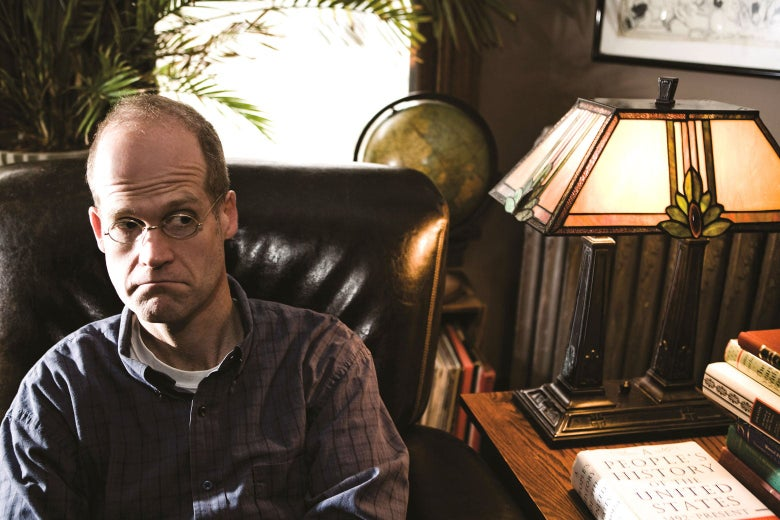 Chris Ware sitting beside a desk.