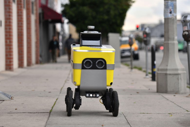A yellow robot with four wheels on a sidewalk.