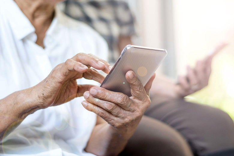 An elderly person's hands hold a smartphone