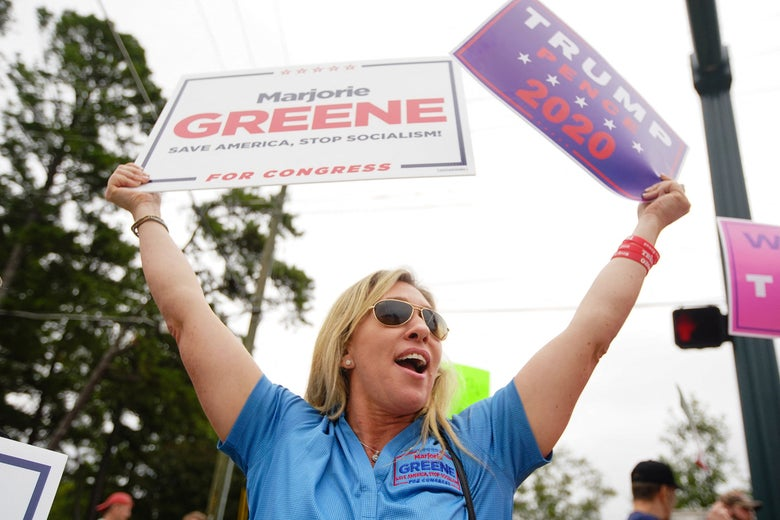 Greene holds up campaign signs in support of her and Donald Trump.