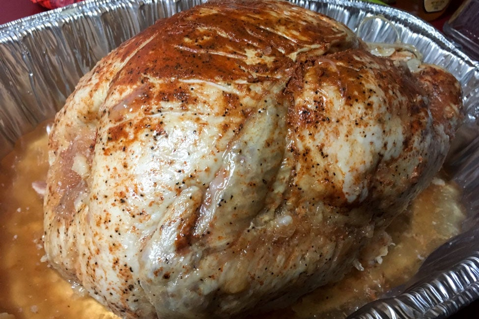 A turkey covered in red-ish seasoning in a foil roasting pan.