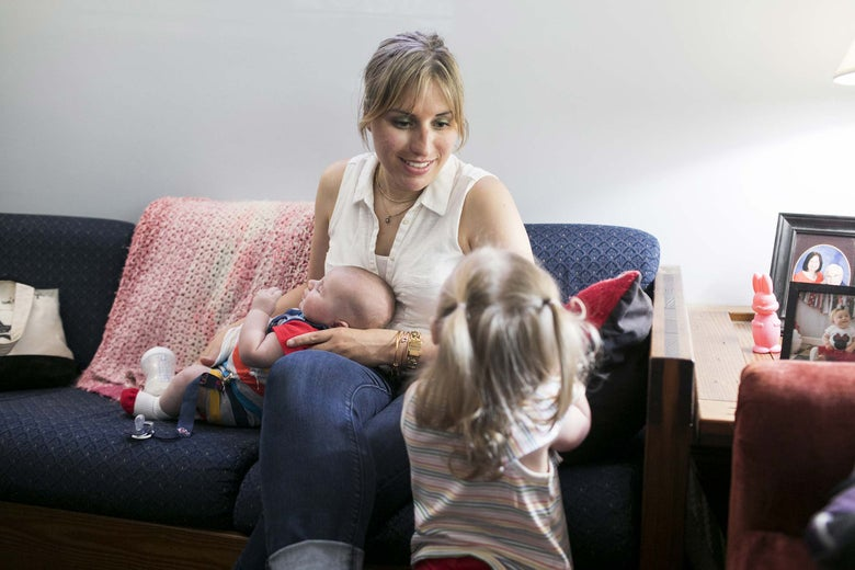 Celeste Blau sits on the couch holding her son Finneas while playing with Clementine.
