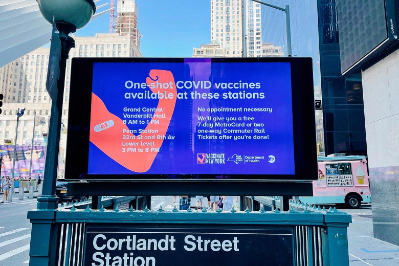 A screen advertising transit rewards for COVID-19 vaccination above the entrance to a subway station