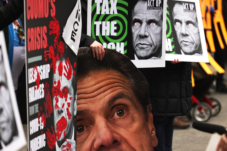 "A row of protesters holding signs with Cuomo's picture on them that say ""Cuomo's Crisis"" and ""Tax the Rich"""