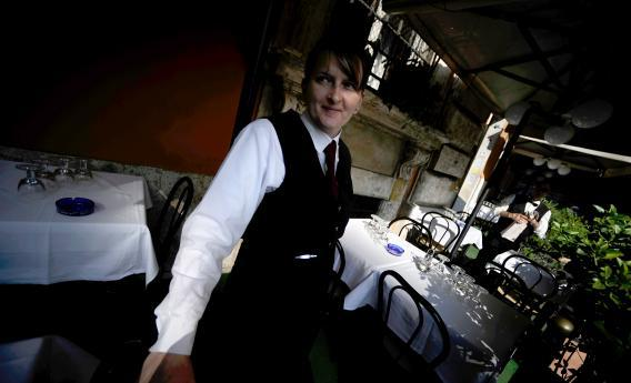 A waitress stands in front of a restaurant in downtown Rome on Nov. 2, 2011