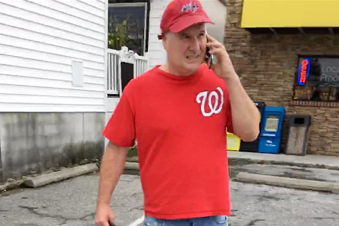 Judge, wearing a red Washington Nationals shirt, speaks on a phone while walking through a parking lot.