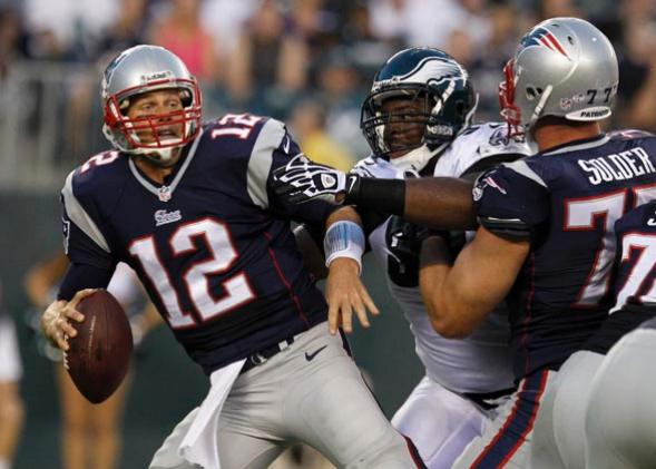 New England Patriots quarterback Tom Brady (12) is held by the Philadelphia Eagles defensive end Fletcher Cox (C) as the Patriots Tackle Nate Solder.