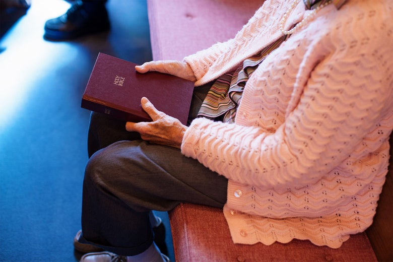 An elderly woman sits in a pew, holding a Bible.